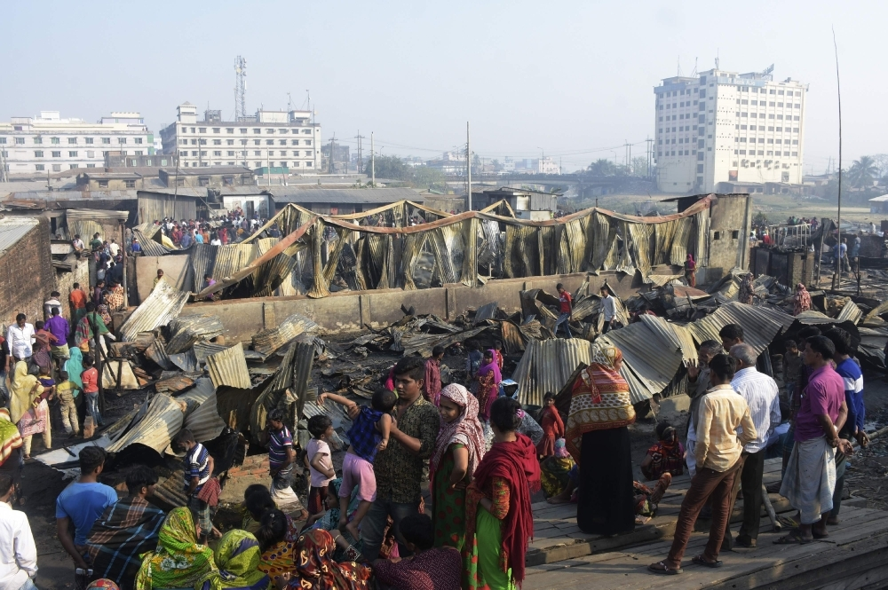 Residents walk past their destroyed houses after a fire broke out in Chittagong on Sunday. — AFP