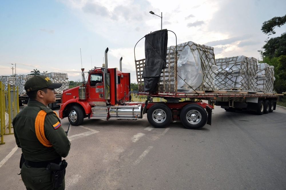 Trucks loaded with humanitarian aid for Venezuela drive toward the Tienditas Bridge in Cucuta, Colombia, on the border with Tachira, Venezuela, on sunday.  Venezuelan opposition leader Juan Guaido on Saturday called for nationwide protests next week to support volunteers planning to travel to the border with Colombia to bring in US humanitarian aid, the latest flashpoint in the country's political crisis.  — AFP