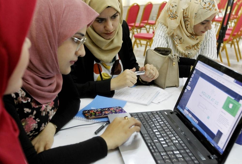 Iraqi girls check a computer at