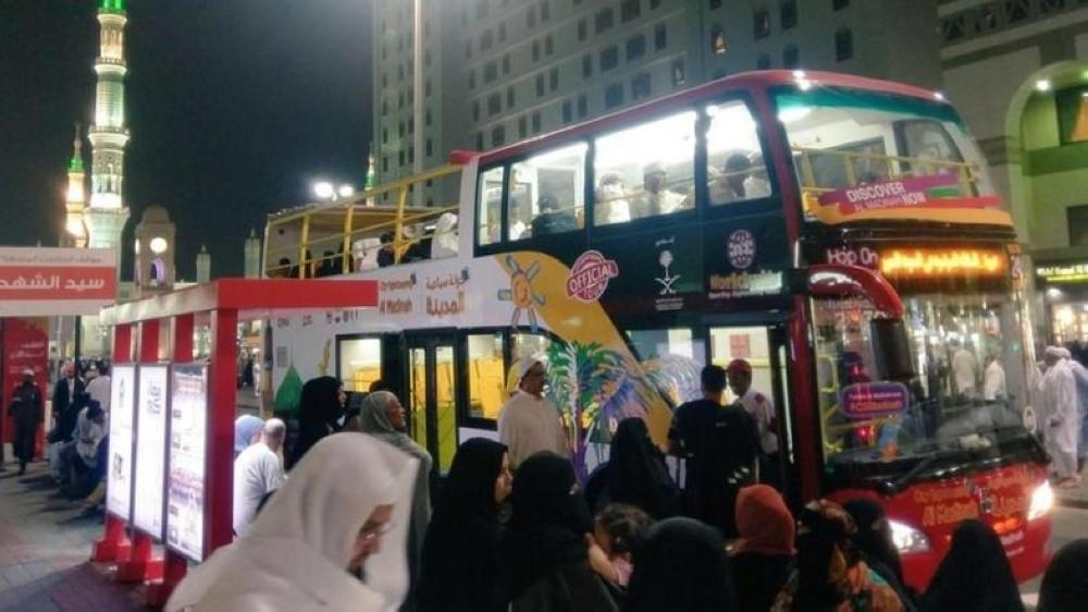 The double decker buses that take visitors to historical sites in Madinah waiting outside the Prophet's Mosque.