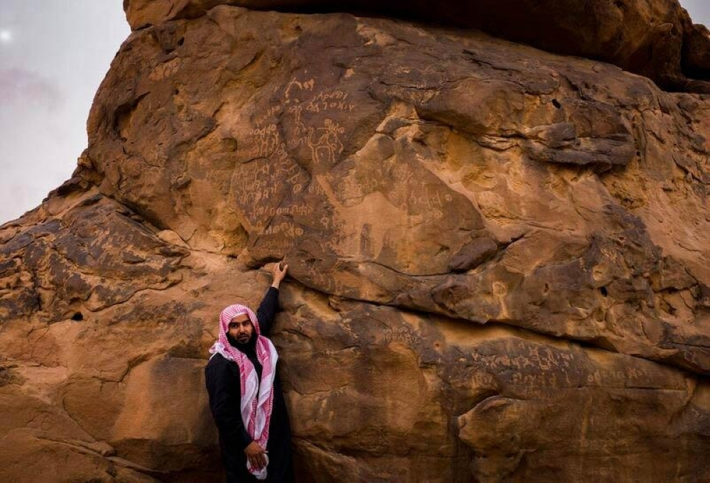 Tour guide Mamdouh Al-Fadhel translates some of the inscriptions at the UNESCO herirtage site in Al-Jubbah.