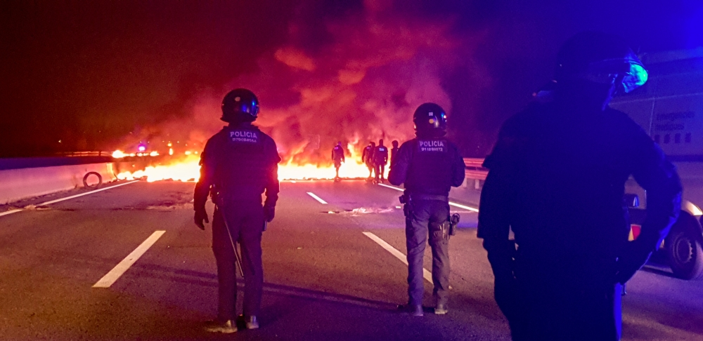 Police officers stand next to burning barricades settled to block the AP7 highway during a regional strike near Girona, Spain, on Thursday. — Reuters