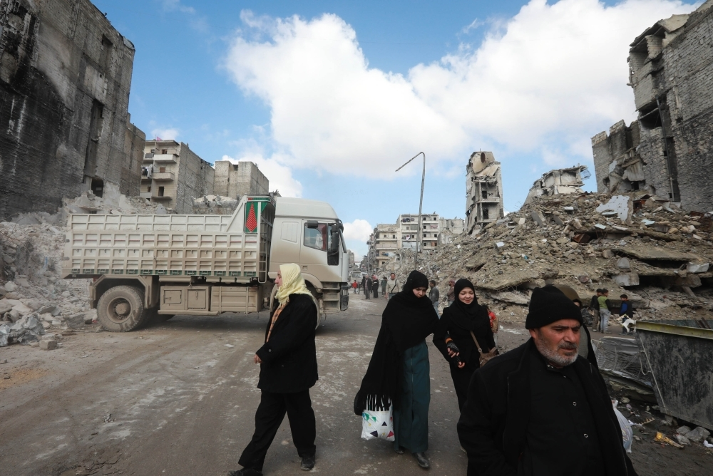 Syrians walk past a truck removing the rubble from a building that was destroyed during battles between rebel fighters and regime forces, in the former opposition held district of Salaheddin in the northern Syrian city of Aleppo, in this Feb. 11, 2019 file photo. — AFP