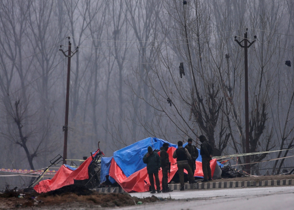 Forensic and security officials stand next to the wreckage of a bus after a suicide bomber rammed a car into the bus carrying Central Reserve Police Force (CRPF) personnel in Lethpora in south Kashmir's Pulwama district in this Feb. 15, 2019 file photo. — Reuters