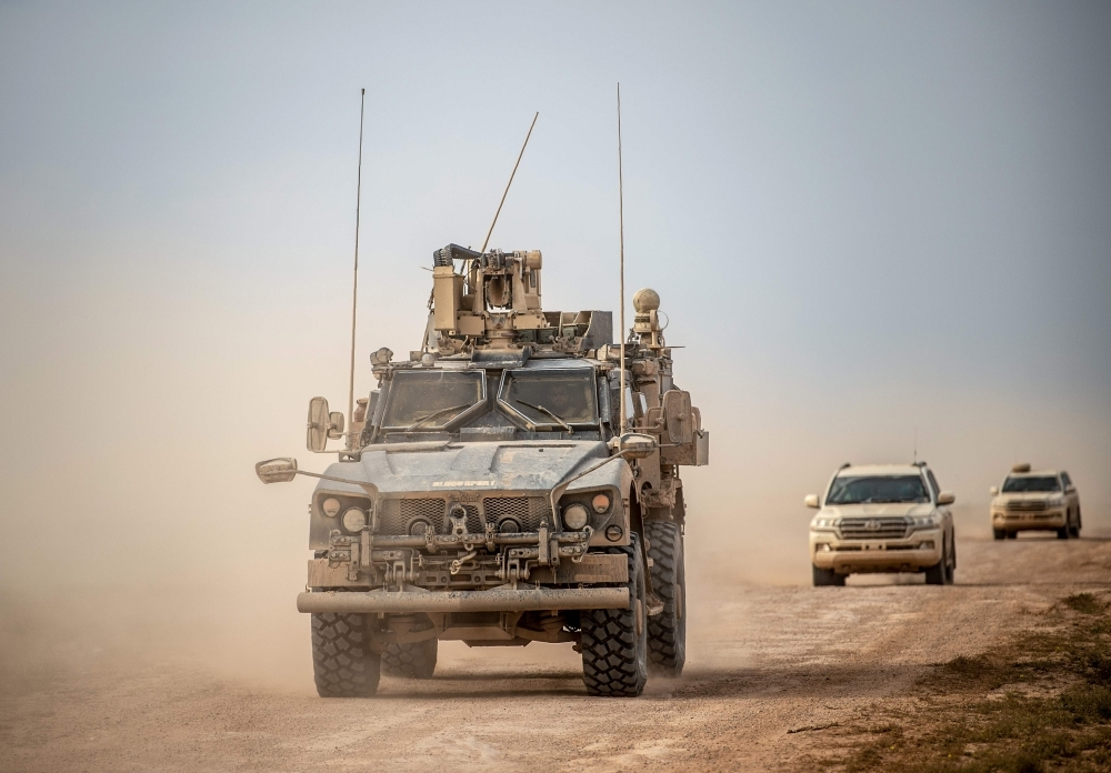 A picture taken on Thursday shows vehicles belonging to the US-backed coalition as they drive down a road in Syria's northern Deir Al-Zor province.  — AFP