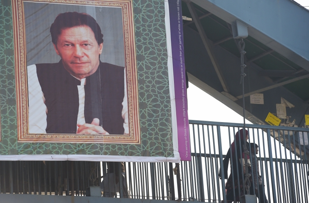 Pakistani civilians walk in an alley behind a poster displaying the portrait of Pakistani Prime Minister Imran Khan in Islamabad in this Feb. 19, 2019 file photo. — AFP