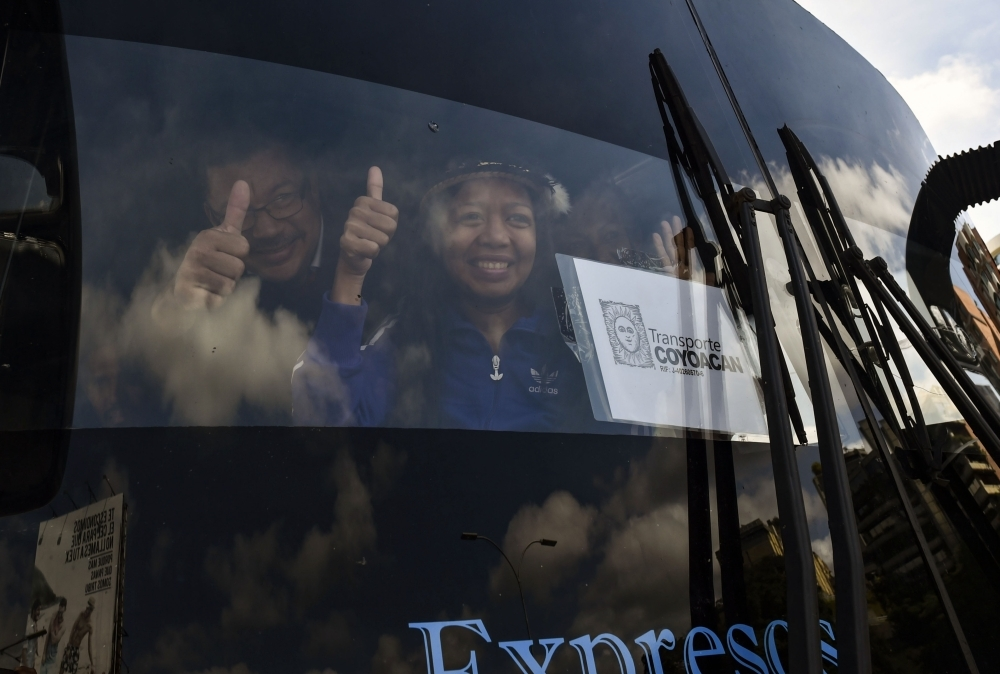 Opposition deputies wave while traveling in a caravan of buses heading to the border with Colombia to bring in US-supplied humanitarian aid, in Caracas on Thursday. — AFP