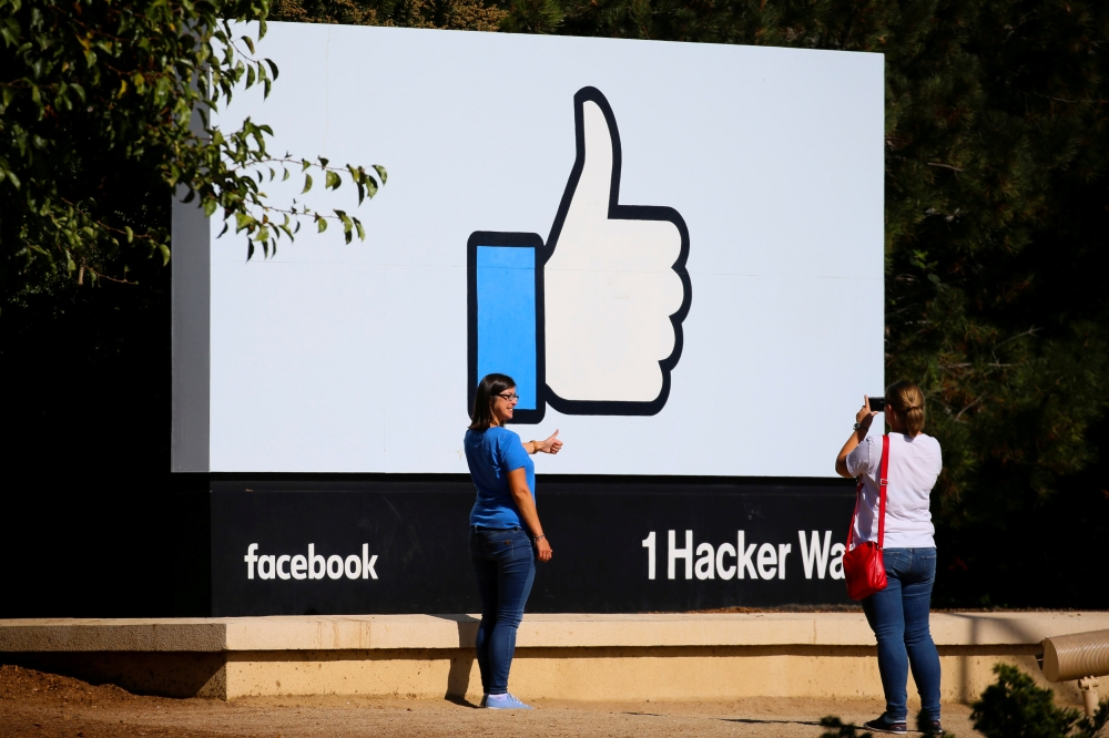 File photo shows two women taking photos in front of the entrance sign to Facebook headquarters in Menlo Park, California. — Reuters