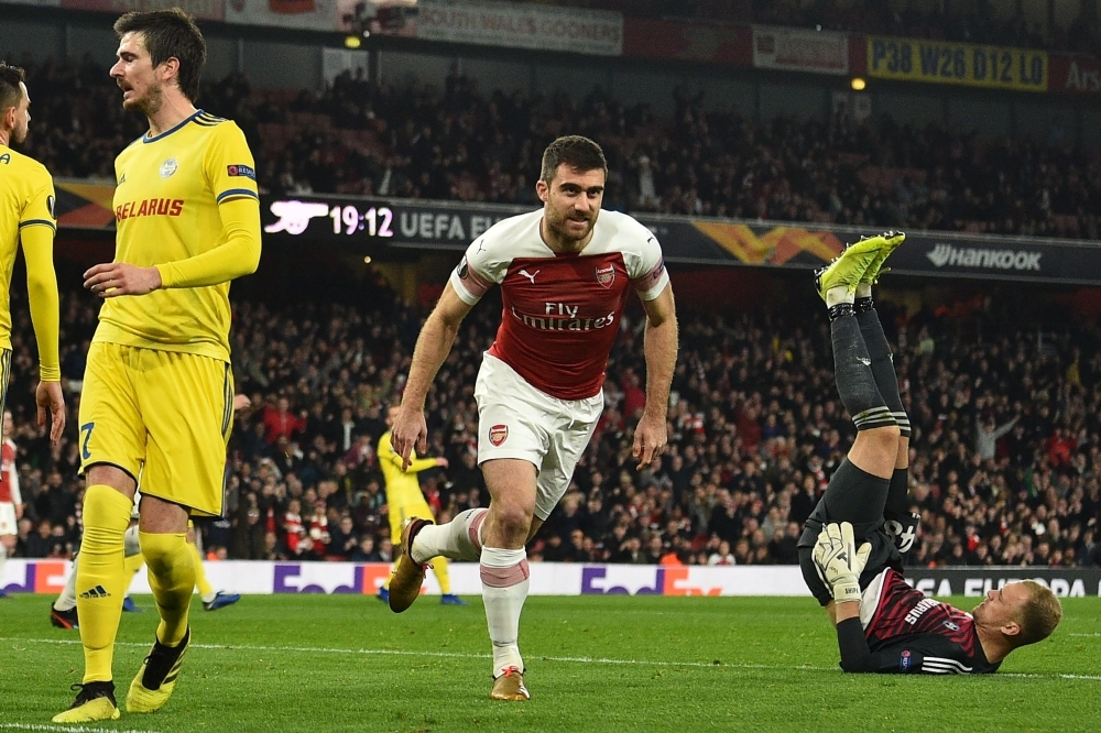 Arsenal's Greek defender Sokratis Papastathopoulos (C) celebrates after scoring their third goal during the UEFA Europa League round of 32, 2nd leg football match between Arsenal and Bate Borisov at the Emirates stadium in London on Thursday. — AFP