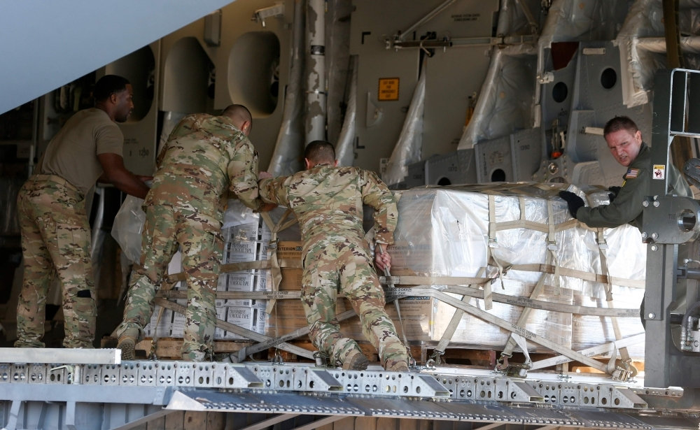 US soldiers load a C-17 cargo plane with food, water and medicine for a humanitarian mission to Venezuela, at Homestead Air Force Base in Homestead, Florida, on Friday. — AFP