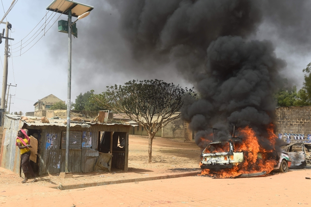 TOPSHOT - A man tries to run away from a rickety road side shop as cars are set on fire following deadly clashes between supporters of the ruling All Progressives Congress (APC) and the opposition Peoples Democratic Party (PDP) at Kofa in Bebeji district of Kano, economic nerve center of northern Nigeria, on Friday. — AFP