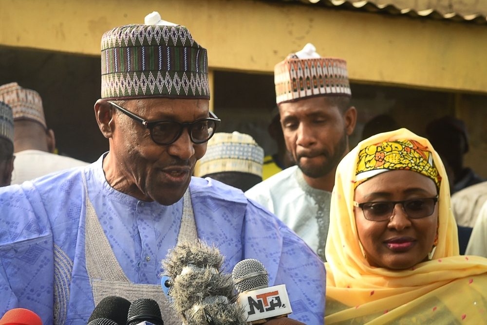 Candidate of the All Progressives Congress (APC) and incumbent President Muhammadu Buhari (left), flanked by his wife Aisha Buhari, speaks after voting at a polling station in his native hometown Daura in Katsina State, northwest Nigeria, Saturday. — AFP