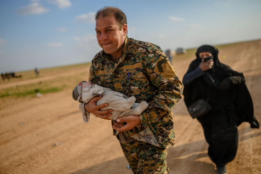 A member of the Kurdish-led Syrian Democratic Forces (SDF) carries a baby followed by the mother who cries and asks for help after leaving the Daesh group's last holdout of Baghouz, in Syria's northern Deir Ez-Zor province. — AFP photos