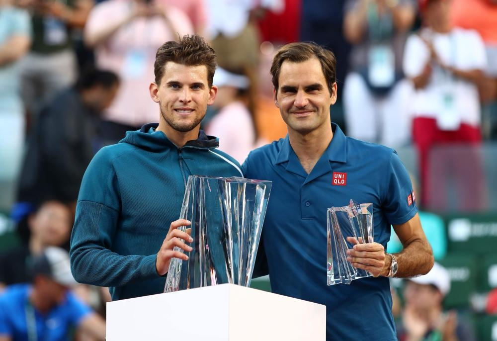 Dominic Thiem (L) of Austria holds the championship trophy after beating Roger Federer (R) of Switzerland at the BNP Paribas Open final in Indian Wells, California, Sunday. — AFP