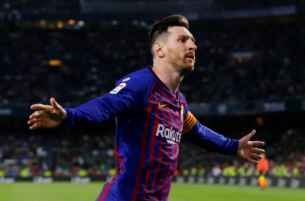 Barcelona's Lionel Messi celebrates scoring their fourth goal to complete his hat trick in La Liga Santander match against Real Betis at Estadio Benito Villamarin, Seville, Sunday. — Reuters