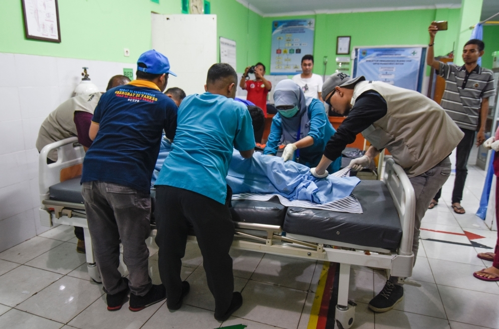 Indonesian medics move the body of a Malaysian national killed in a landslide caused by a 5.5-magnitude earthquake at Tiu Kelep waterfall, in Bayan on the resort island of Lombok, on Sunday. — AFP