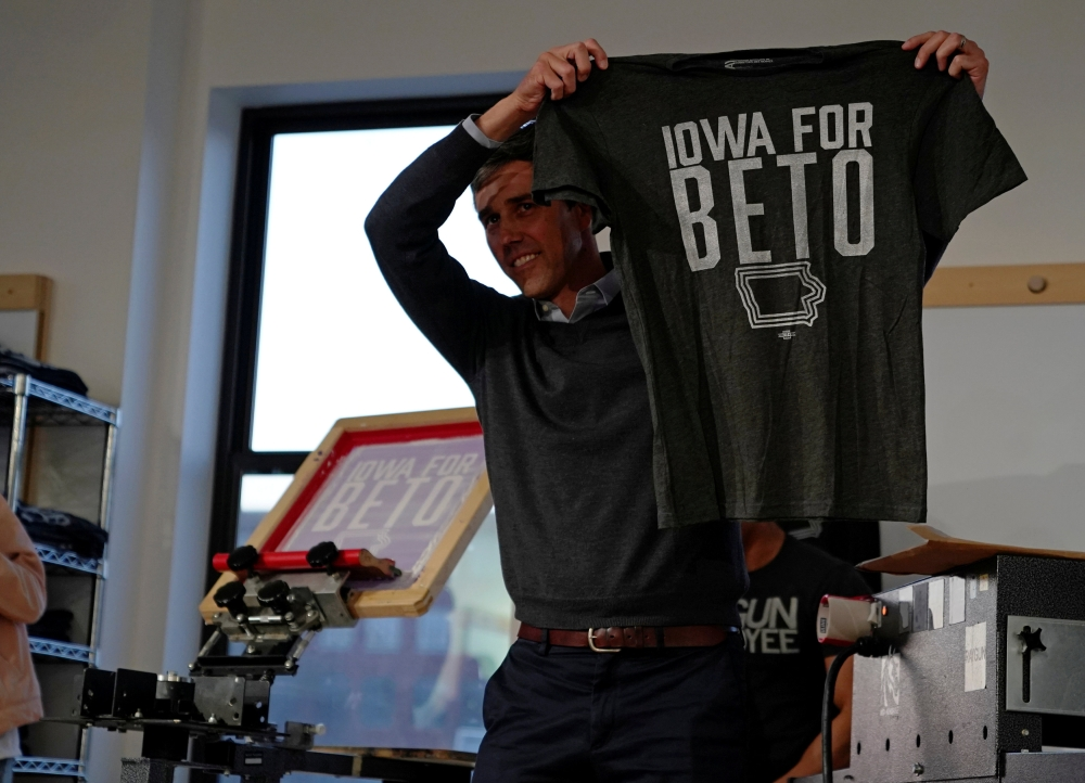 "Democratic 2020 presidential candidate Beto O'Rourke, 46, holds up a ""Iowa For Beto"" screen-printed shirt at Raygun clothing store during a three day road trip across Iowa, in Cedar Rapids, Iowa, in this March 15, 2019 file photo. — Reuters"