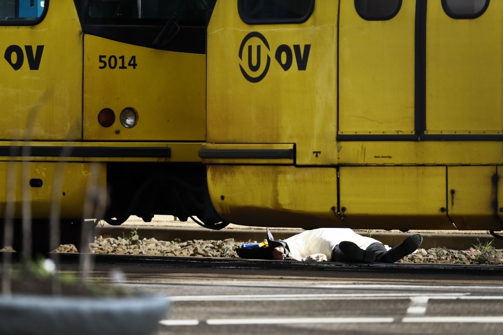 A body lying on the ground is covered near a tram at the 24 Oktoberplace in Utrecht Monday where a shooting took place. — AFP