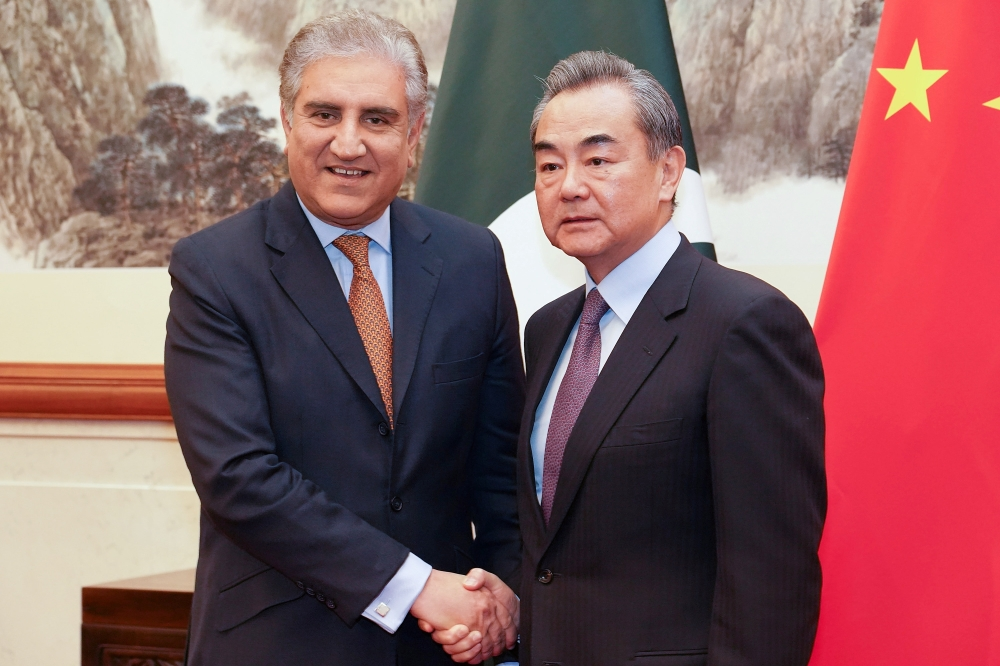 Chinese Foreign Minister Wang Yi shakes hands with Pakistani Foreign Minister Shah Mehmood Qureshi during a meeting at Diaoyutai State Guesthouse in Beijing, China, on Tuesday. — Reuters