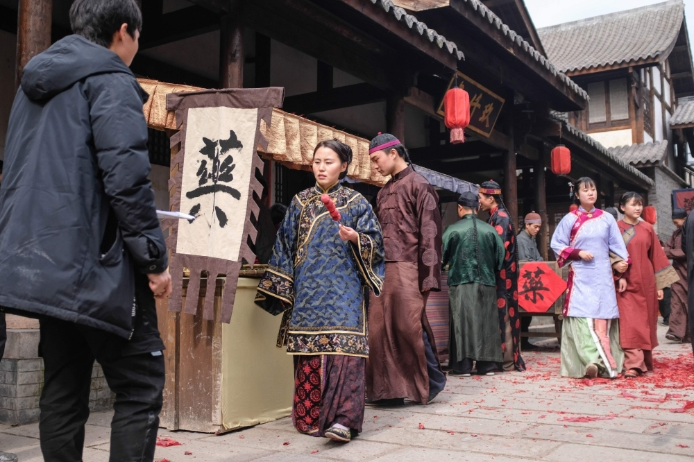 Extras dressed in period costume walking on set during filming for a Chinese TV drama at Hengdian World Studios in Dongyang in China's eastern Zhejiang province. — AFP