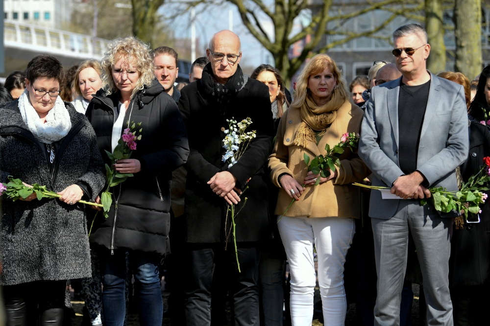 People hold flowers at a makeshift memorial at the site of a tram shooting in Utrecht, Netherlands, on Tuesday. — Reuters