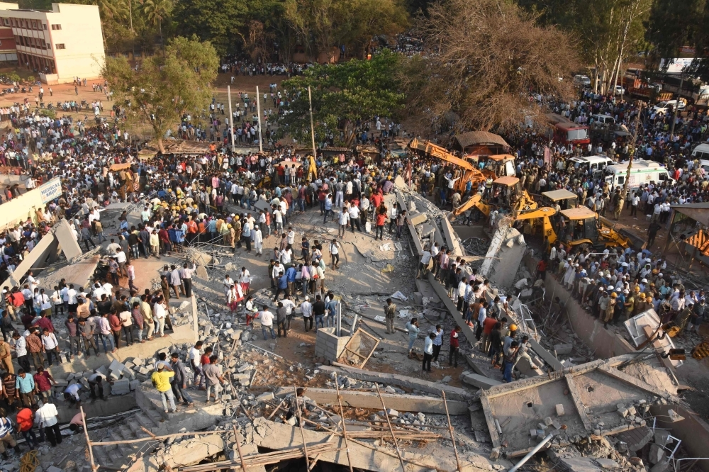 Onlookers gather near the rubble while rescue teams search for survivors after an under-construction multi-story building collapsed in Dharwad district of Karnataka on Tuesday. — AFP