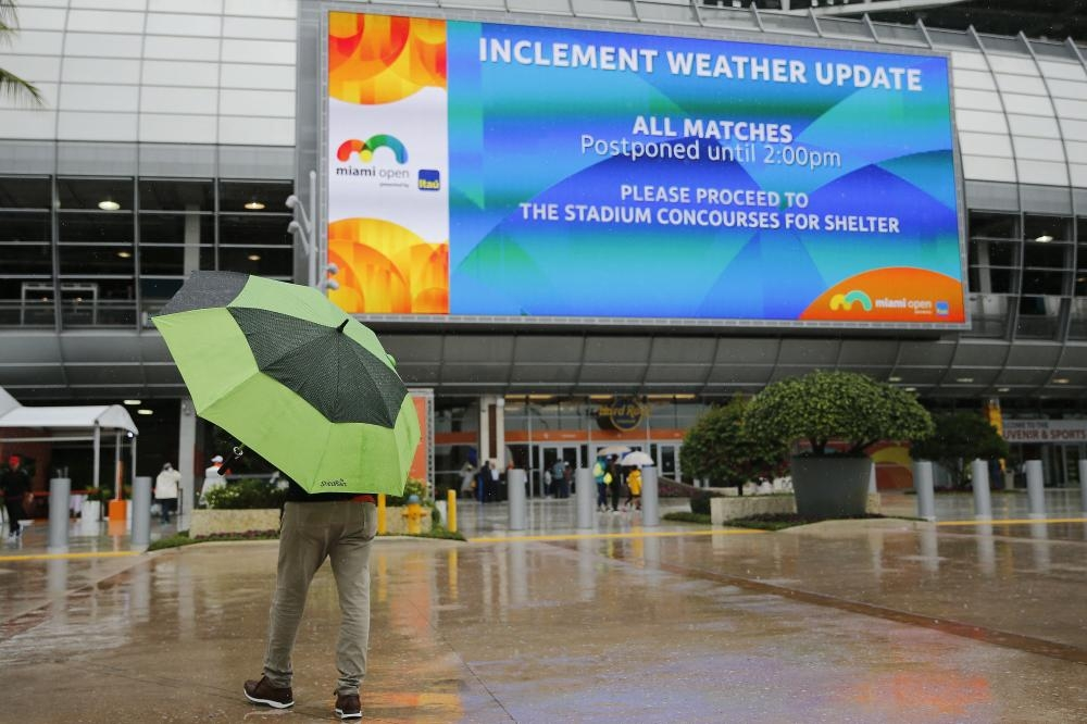 Fans walk through the tennis complex as matches are postponed on Day 2 of the Miami Open in Miami Gardens, Florida, Tuesday. — AFP