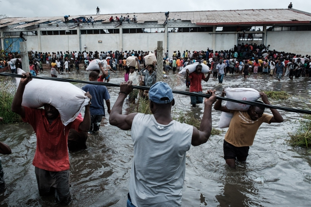 "People take part in the looting sacks of Chinese rice printed ""China Aid"" from a warehouse which is surrounded by water after cyclone hit in Beira, Mozambique, on Wednesday. — AFP"