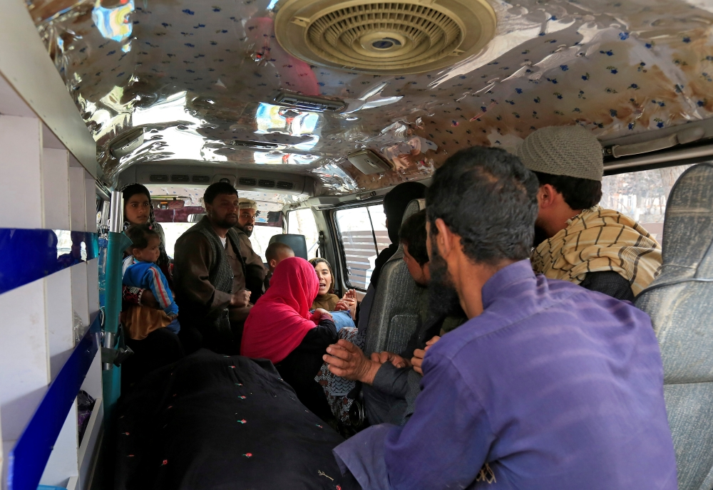 A family reacts inside an ambulance after they lost a family member after multiple explosions in Kabul, Afghanistan, on Thursday. — Reuters