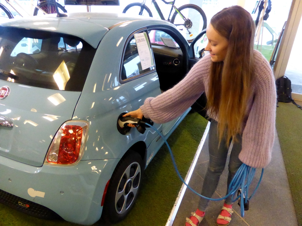 Maiken Skram of Buddy Electric car dealer company shows the charging of a second-hand Fiat 500e, imported from California, US, in Oslo, Norway. — Reuters
