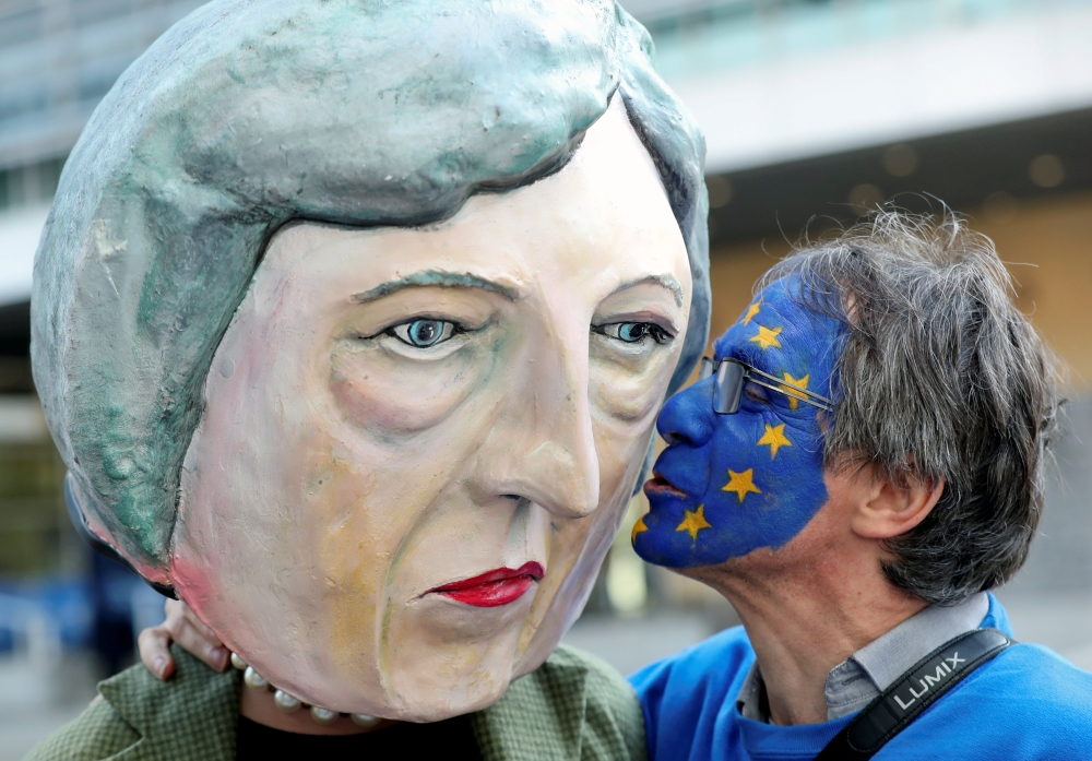 An anti-Brexit demonstrator kisses a protester dressed as Britain's Prime Minister Theresa May ahead of a EU Summit in Brussels, Belgium, on Thursday. — Reuters