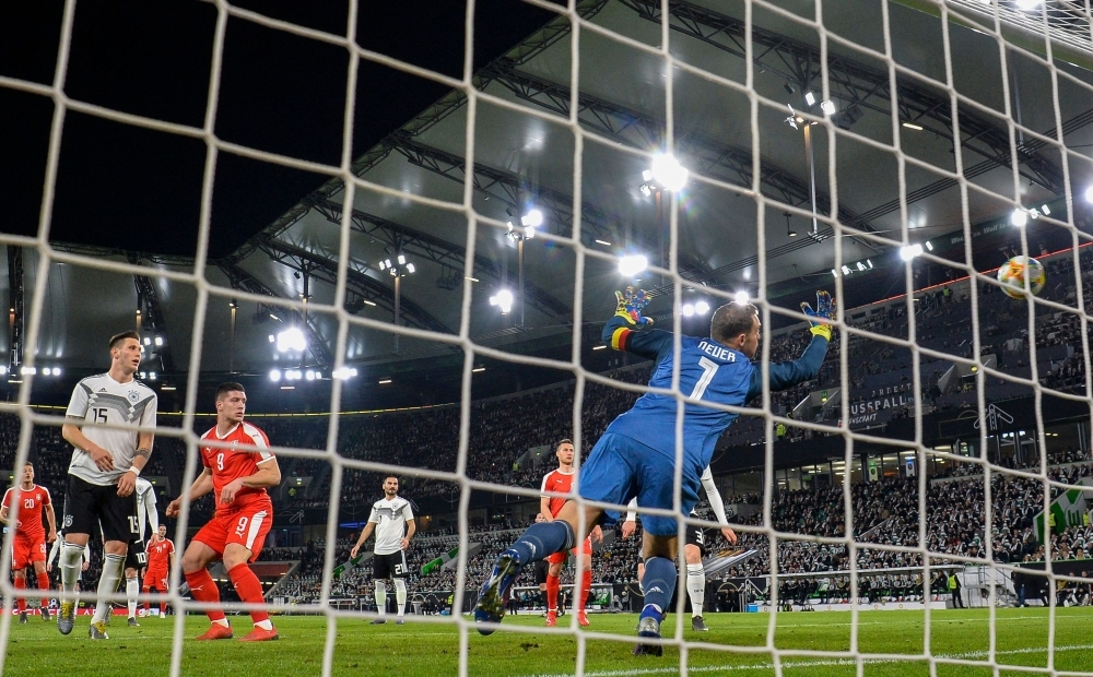 Serbia's forward Luka Jovic (2nd from L) hits the ball past Germany's goalkeeper Manuel Neuer during the friendly football match Germany v Serbia in Wolfsburg, western Germany on Wednesday. — AFP