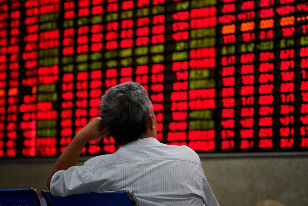 An investor looks at an electronic board showing stock information at a brokerage house in Shanghai, China, in this file photo. — Reuters