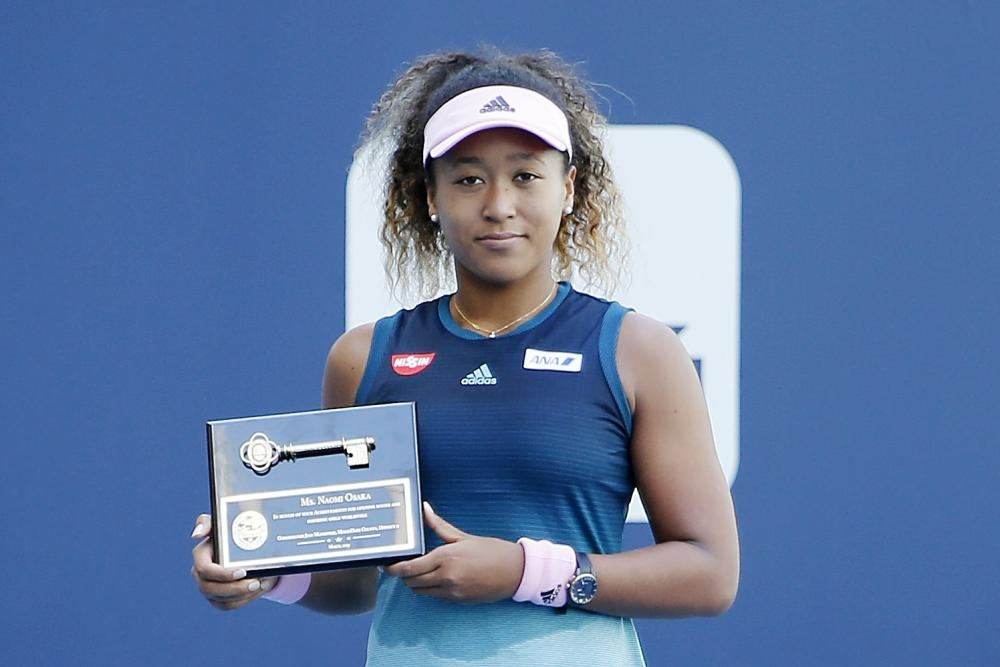 """Naomi Osaka of Japan poses for a photo after being presented with the """"Key to the County"""" at the Miami Open in Miami Gardens, Florida, Friday. — AFP"""