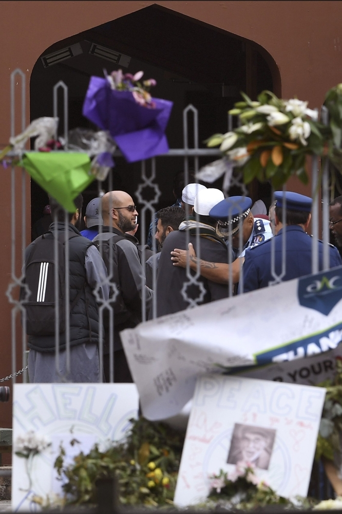 Members of the local Muslim community wait to enter the Al Noor Mosque as it is reopened in Christchurch, Saturday. — AFP