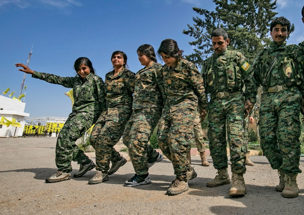 Fighters of the US-backed Kurdish-led Syrian Democratic Forces (SDF) dance as they celebrate near the Omar oilfield in the eastern Syrian Deir Ezzor province on Saturday, after announcing the total elimination of the Daesh group's last bastion in eastern Syria. — AFP