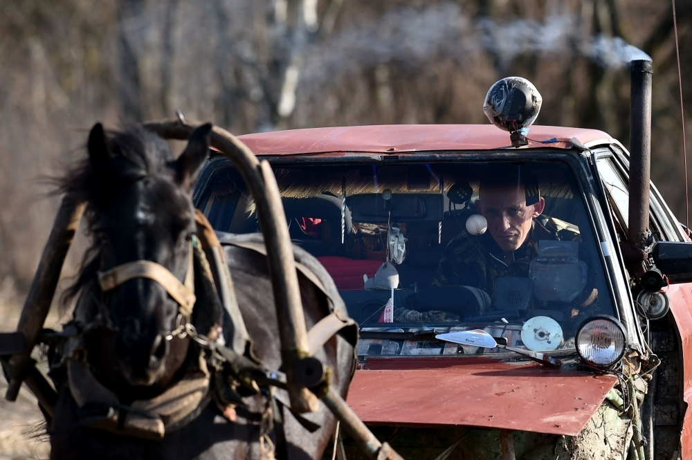 Farmer Alexei Usikov, 31, rides his horse-pulled cart made from an old Audi 80 car in the village of Knyazhitsy, some 230 km east of Minsk. — AFP