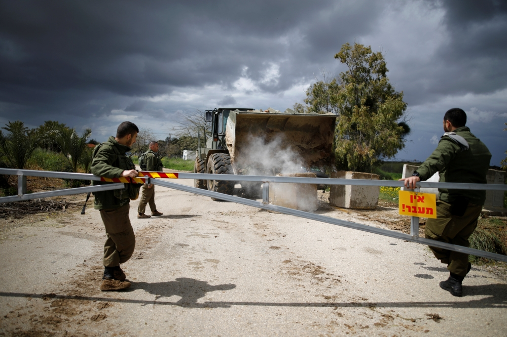 Israeli soldiers watch as a military armored bulldozer moves concrete barricade blocks to close a road near the border with Gaza, in southern Israel, Monday. — Reuters