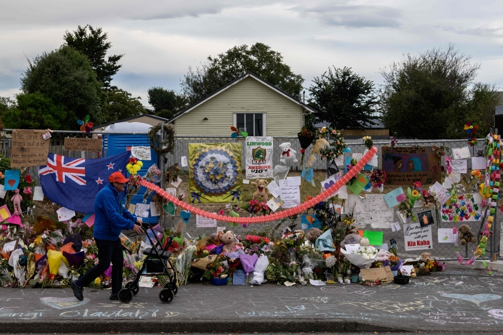 A man man walks past flowers and tributes displayed in memory of the twin mosque massacre victims along the road outside the Linwood mosque, back center, in Christchurch, New Zealand, on Monday. — AFP