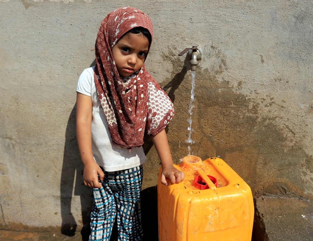 A girl fills a jerry can with drinking water on Salam Street in north Hodeida, Yemen, Monday. — Reuters