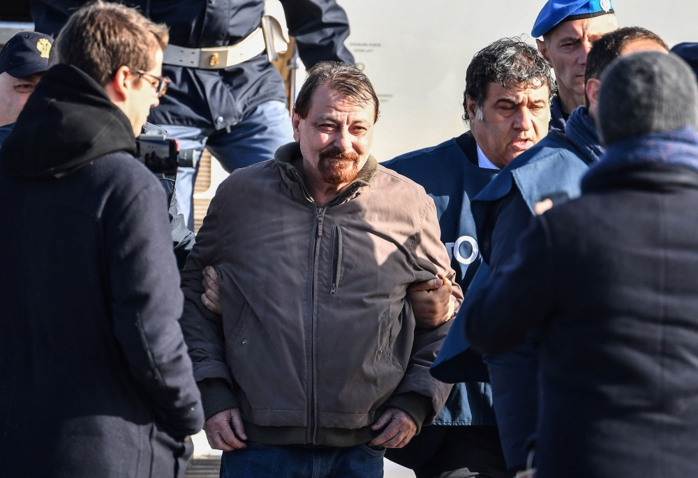 Italian former communist militant Cesare Battisti, center, wanted in Rome for four murders attributed to a far-left group in the 1970s, is escorted by Italian Police officers after stepping off a plane coming from Bolivia and chartered by Italian authorities, after landing at Ciampino airport in Rome in this Jan. 14, 2019 file photo. — AFP