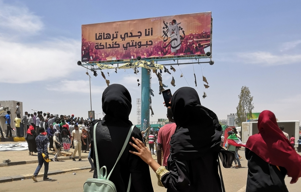 A woman takes a photograph with her smarphone of a billboard showing a reproduction of a picture of Alaa Salah, a Sudanese woman who has become an icon of the protest movement after a video of her leading demonstrators' chants went viral, in the capital Khartoum. — AFP