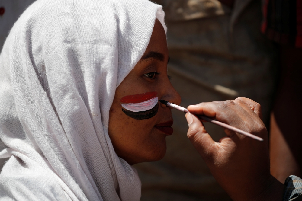 A man paints the Sudanese flag on a demonstrator's face in Khartoum, Sudan, Tuesday. — Reuters