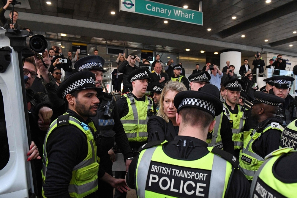 Police escort away an arrested female climate change protester, center, who had glued herself to the roof of a DLR train at Canary Wharf station, on the third day of an environmental protest by the Extinction Rebellion group, in London on Wednesday. — AFP