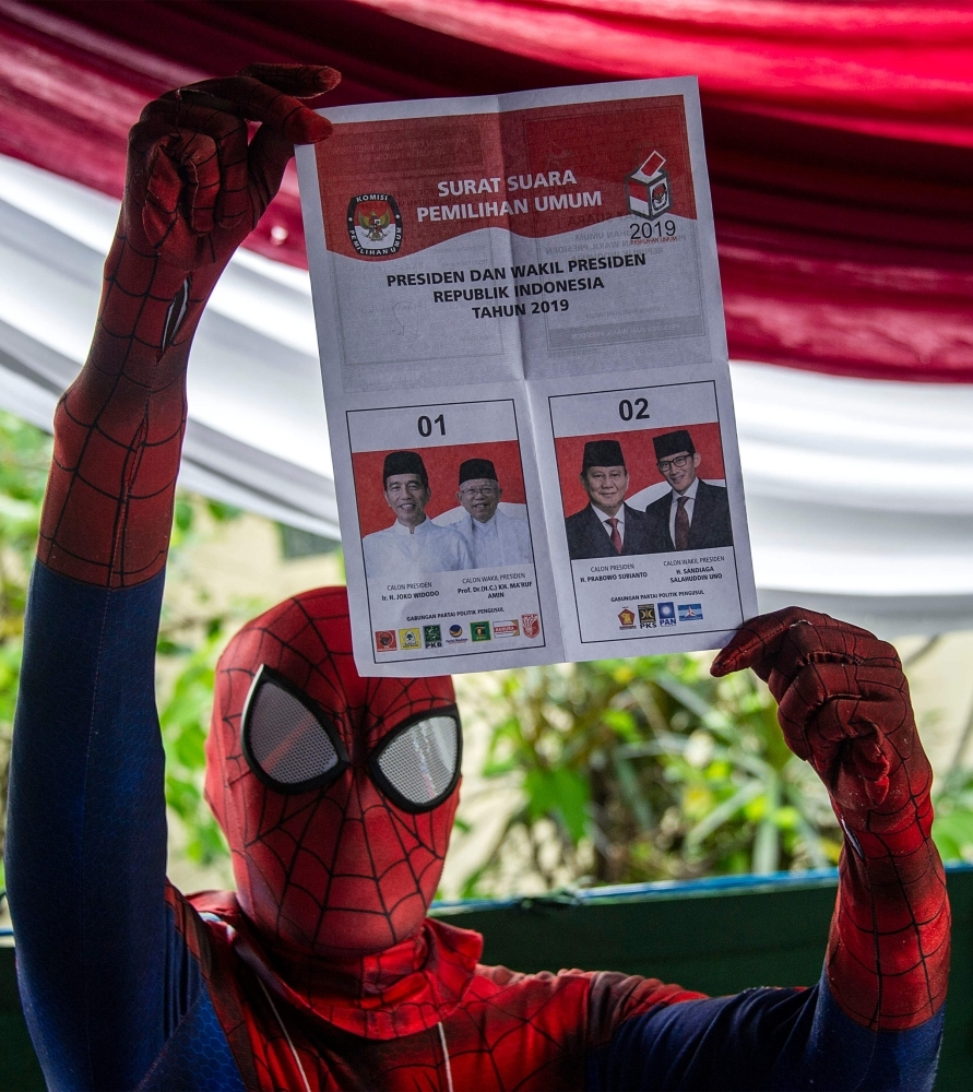 An Indonesian election worker dressed in a superhero costume holds up a ballot paper at a polling station in Surabaya on Wednesday. — AFP