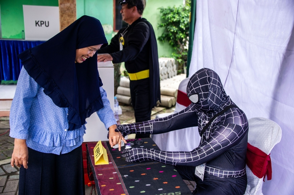 Indonesian election workers dressed in superhero costumes register voters at a polling station in Surabaya on on Wednesday. — AFP