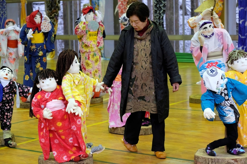 Local resident Tsukimi Ayano checks on a life-size doll displayed at an elementary school, which closed seven years ago as there was no one left to teach, in the tiny village of Nagoro in western Japan, in this March 16, 2019 file photo. — AFP