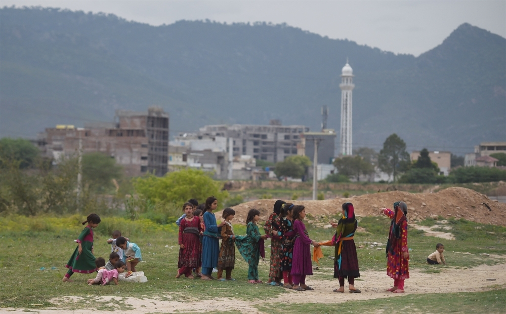Pakistani and Afghan refugee girls play on a ground in the outskirts of Islamabad on Tuesday. — AFP