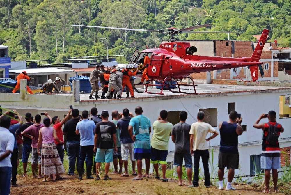 People watch as an injured person is carried onto a rescue helicopter after two buildings collapsed in Muzema, Rio de Janeiro, Brazil, in this April 12, 2019 file photo. — AFP