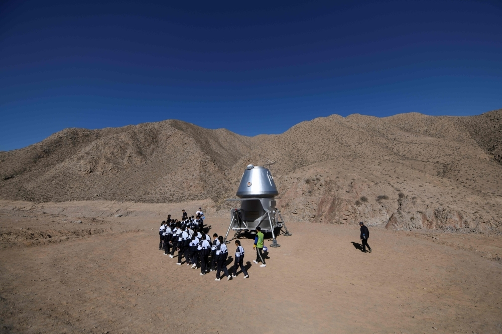 A group of students walk past a model of a lander at